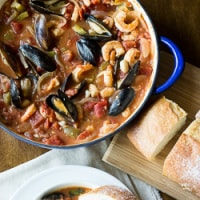 A big pot of seafood coping with a side of bread