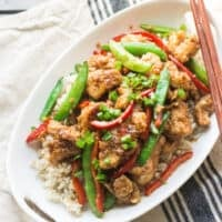 Mongolian chicken with snap peas and bell peppers in a large oval white dish with chopsticks