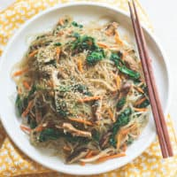 a close up shot of vegetarian japchae plated on a white plate with wooden chopsticks