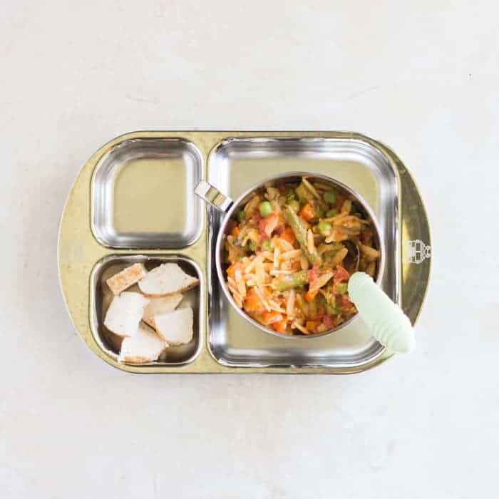 a baby's portion of orzo primavera served on a sectioned stainless steel plate with a side of diced cooked chicken