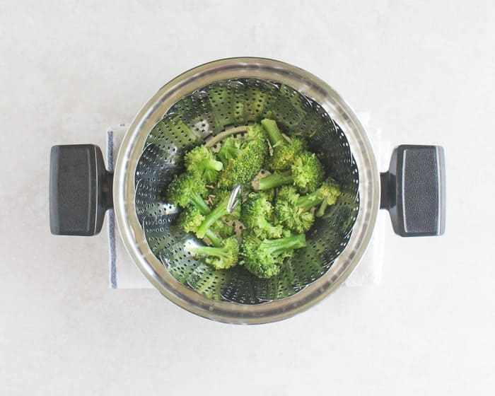 broccoli florets in a large pot with steaming basket