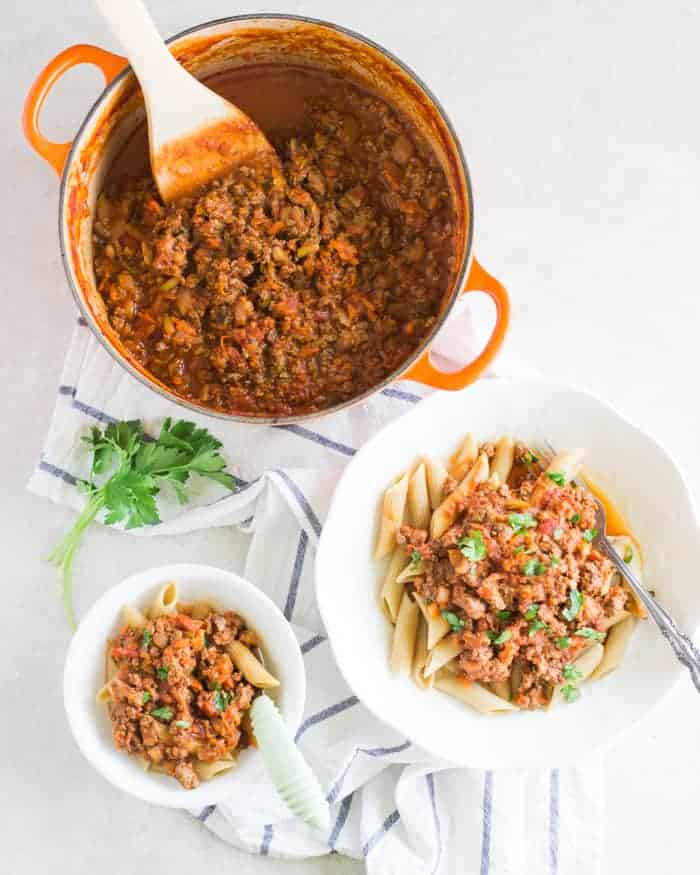 a large pot of meat sauce and an adult portion of sauce over pasta on a white plate as well as a small bowl for a baby