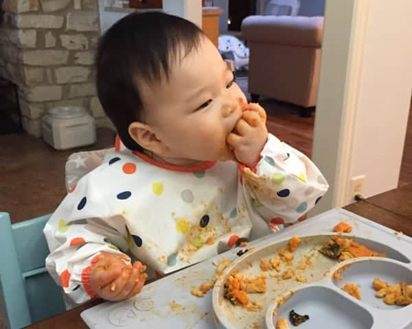 baby happily eating curry from a grey divided plate