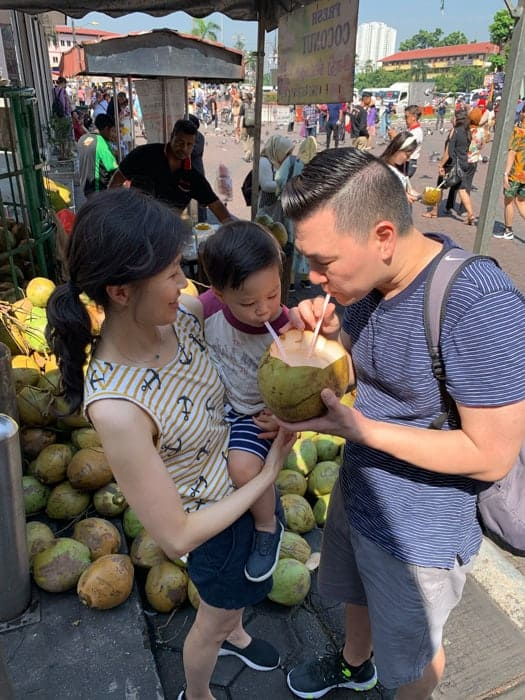 mom holding toddler who's drinking coconut water with dad