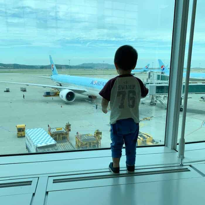 toddler looking out at the plane inside an airport