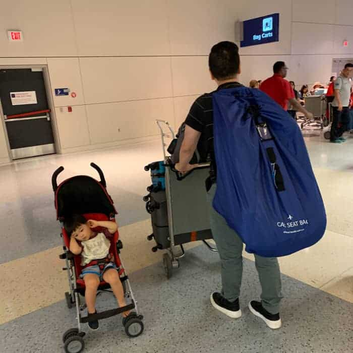 toddler sitting on a stroller with dad carrying luggage and carseat strapped to his back