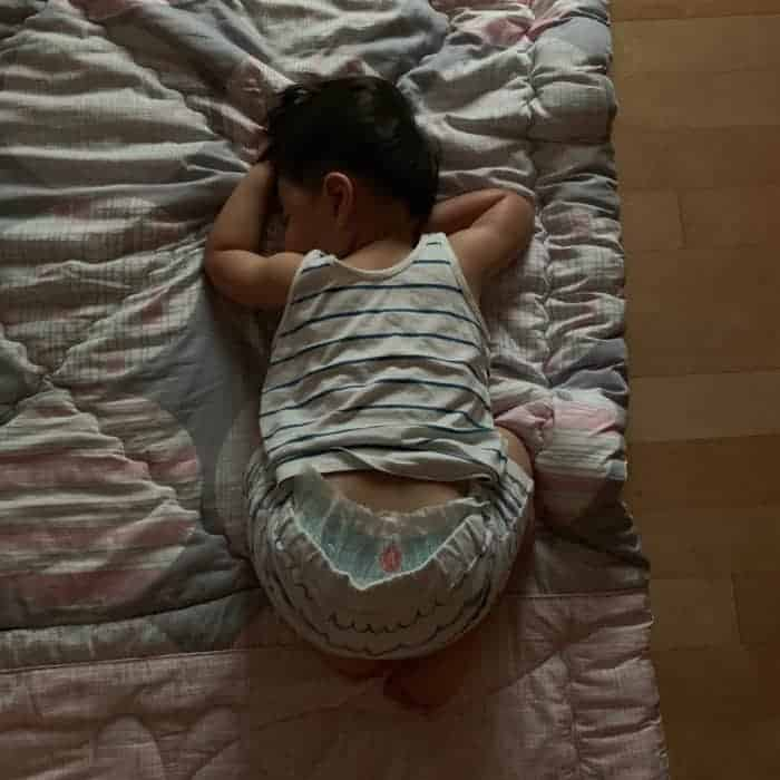 toddler sleeping on the floor on his stomach