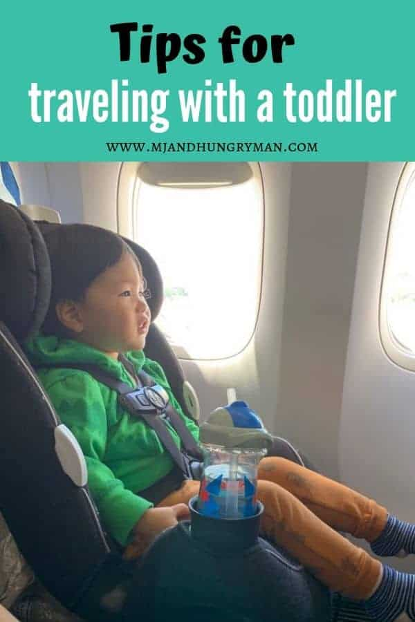 toddler sitting on a carseat on the airplane