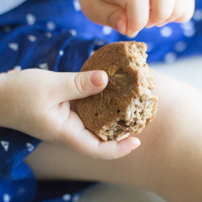 toddler's hands holding an eaten apple cinnamon muffin