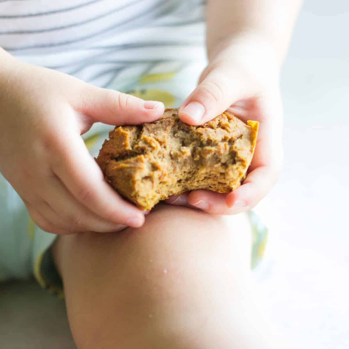 a toddler's hand holding a half eaten muffin