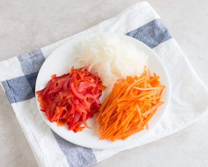 thinly sliced onion, red bell peppers, an carrots on a white plate