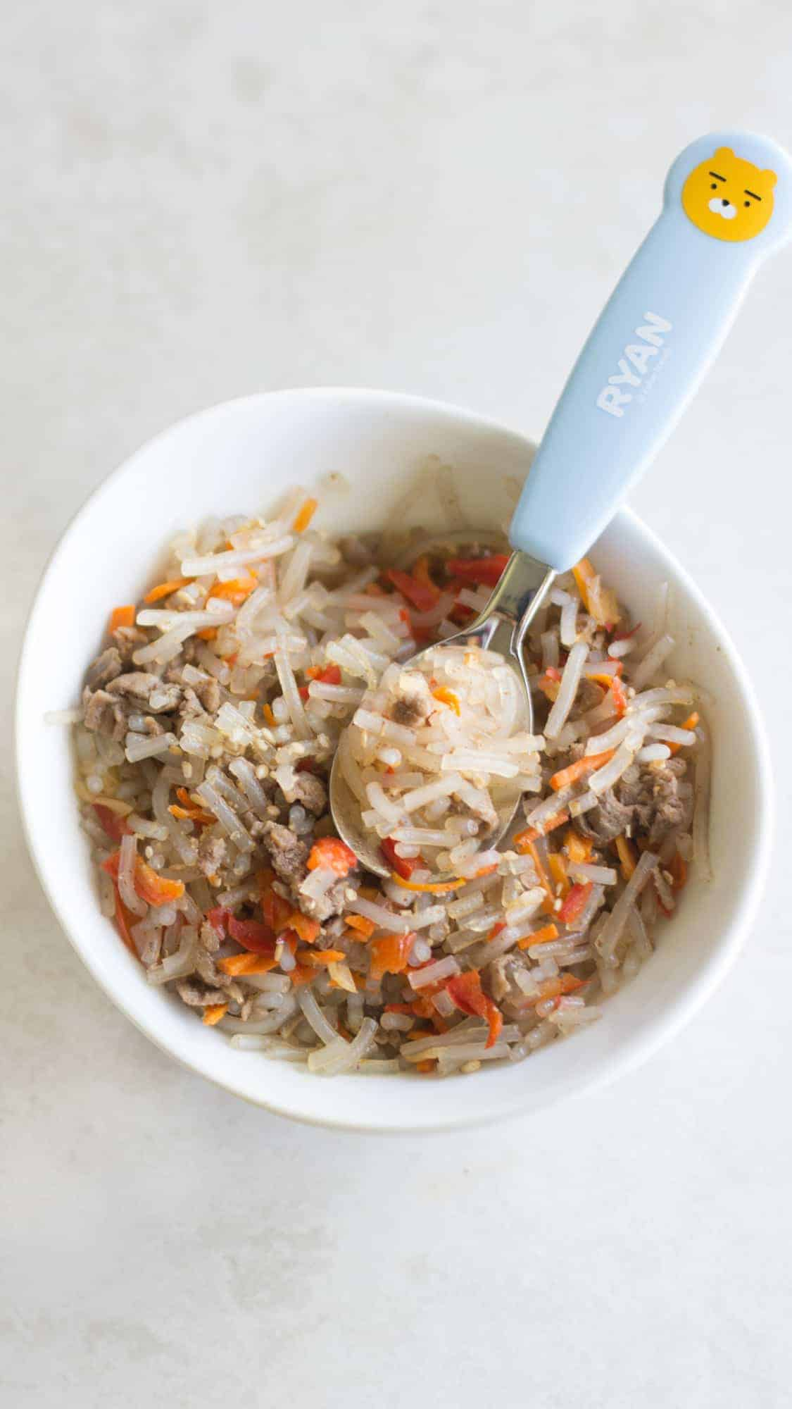 japchae cut into small strands for baby with a baby spoon
