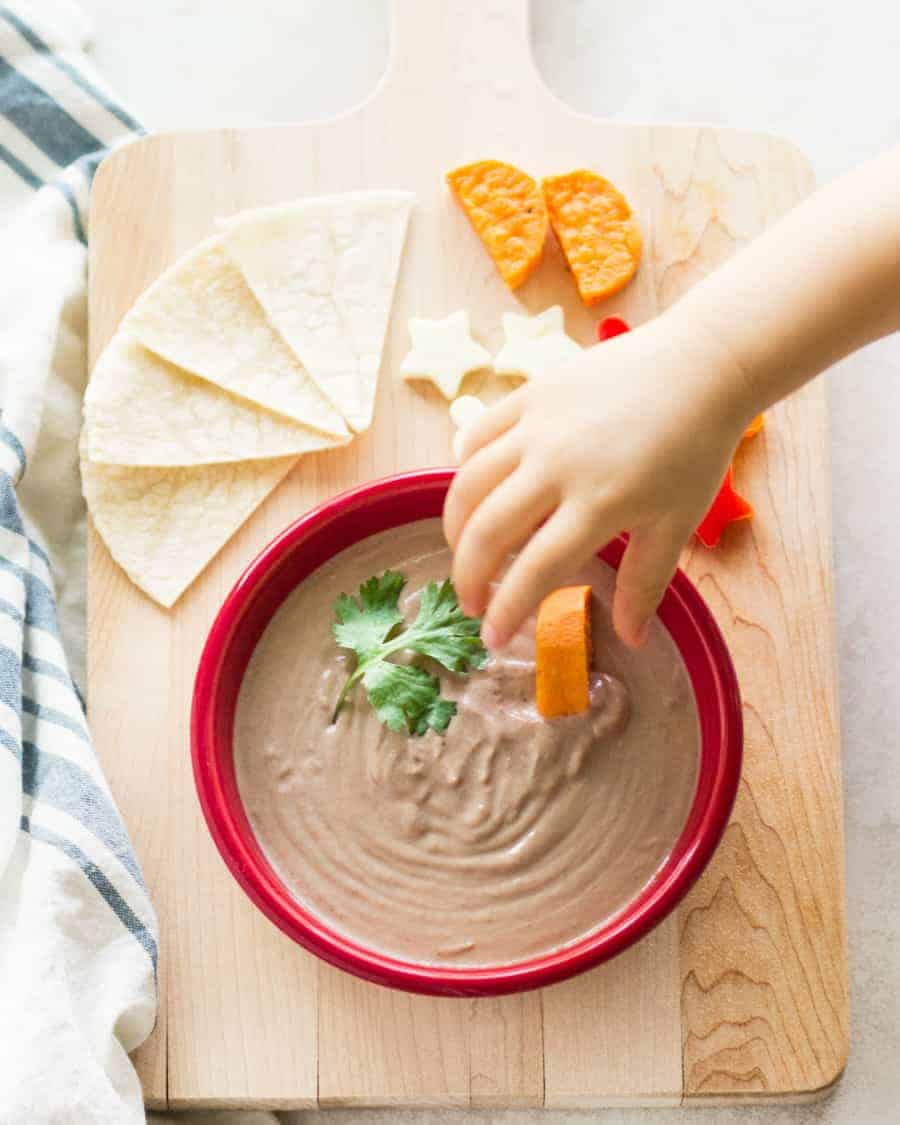 yogurt bean dip in a red bowl with toddler's hand dunking a sliced sweet potato