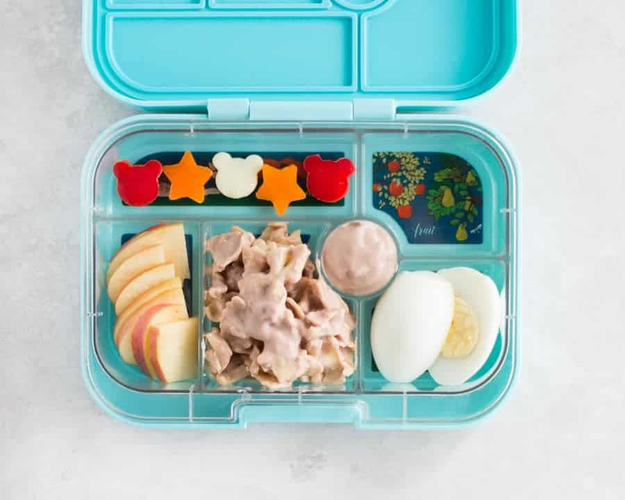 a blue lunchbox with pasta tossed in yogurt bean dip, hard boiled egg, sliced apples, and fun-shaped bell peppers