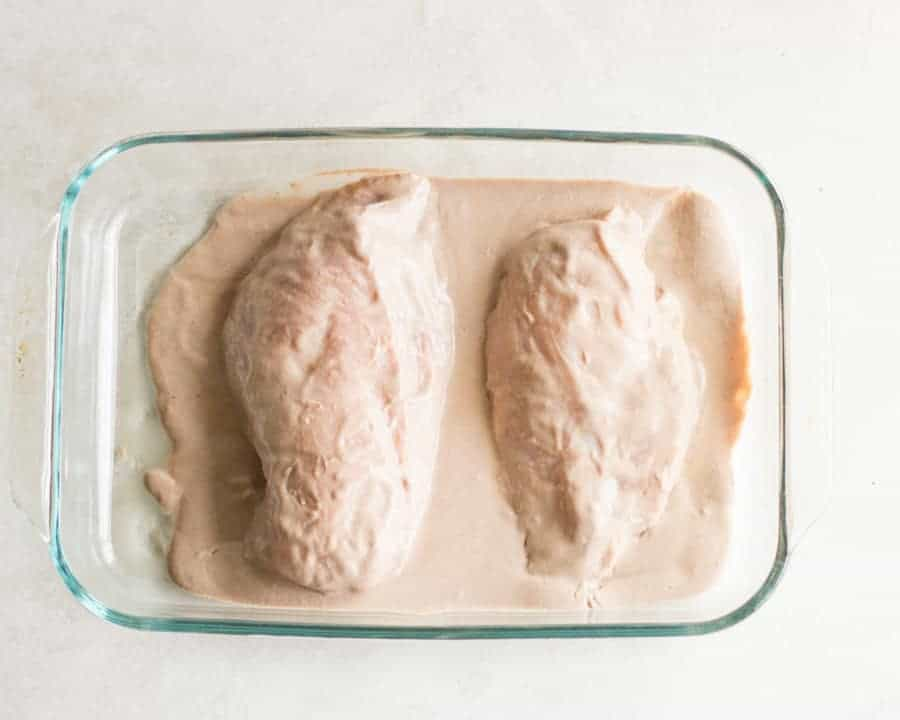 two chicken breasts in a glass oven safe dish with the yogurt marinade poured over