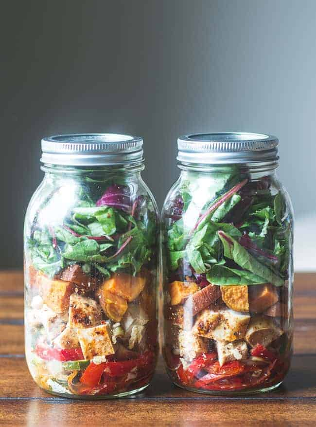 2 mason jars with from bottom to top bell peppers, chicken, sweet potatoes, and greens