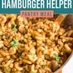 a close up shot of the hamburger helper in a large dutch oven with fresh parsley and a large orange spatula