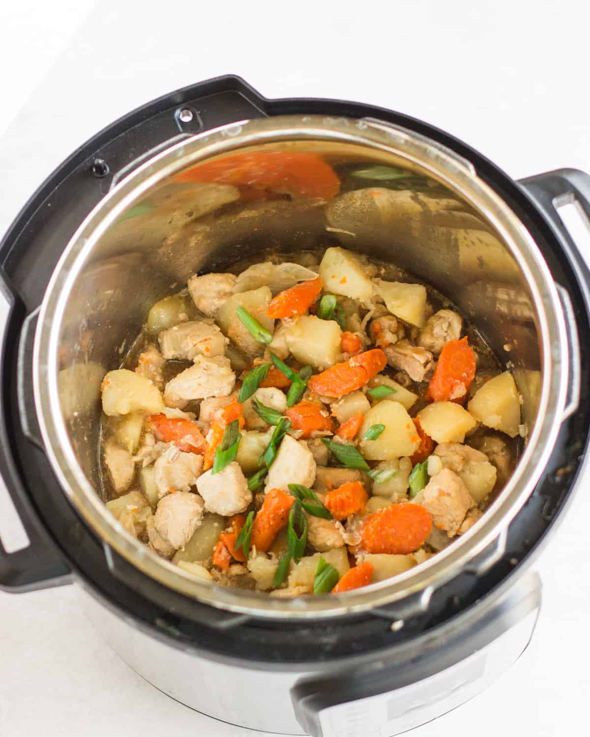 cooked chicken, carrots, potatoes with green onion inside an instant pot