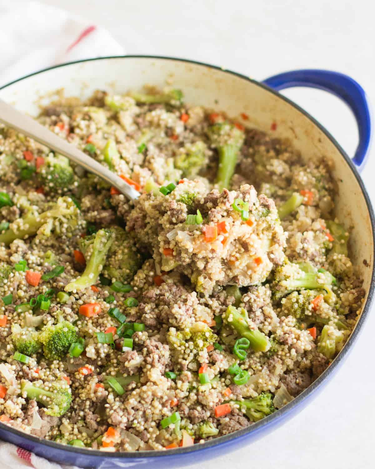 ground beef and broccoli quinoa in a large blue skillet with a small amount scooped onto an orange spatula