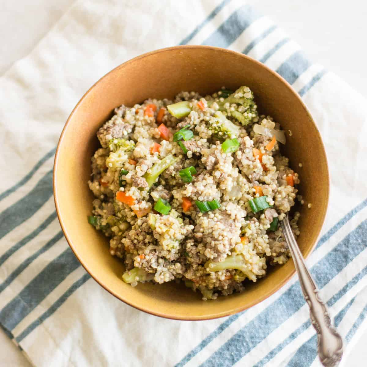 ground beef, carrots, broccoli, and scallion in a brown bowl with a spoon laid on top of folded blue and white striped napkin