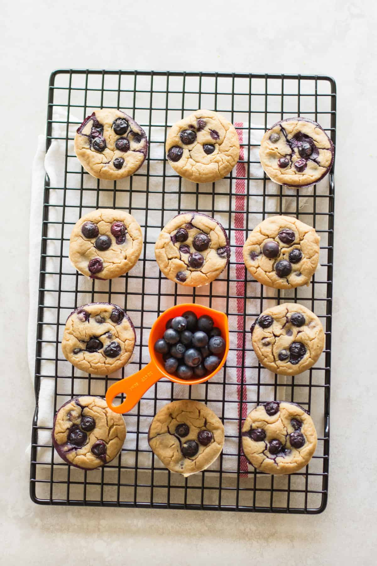 Blueberry muffins cooling on a wire rack with a cup of fresh blueberries