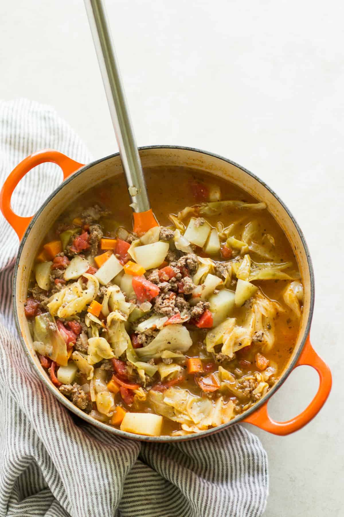 cooked vegetable soup in a dutch oven with a large spatula