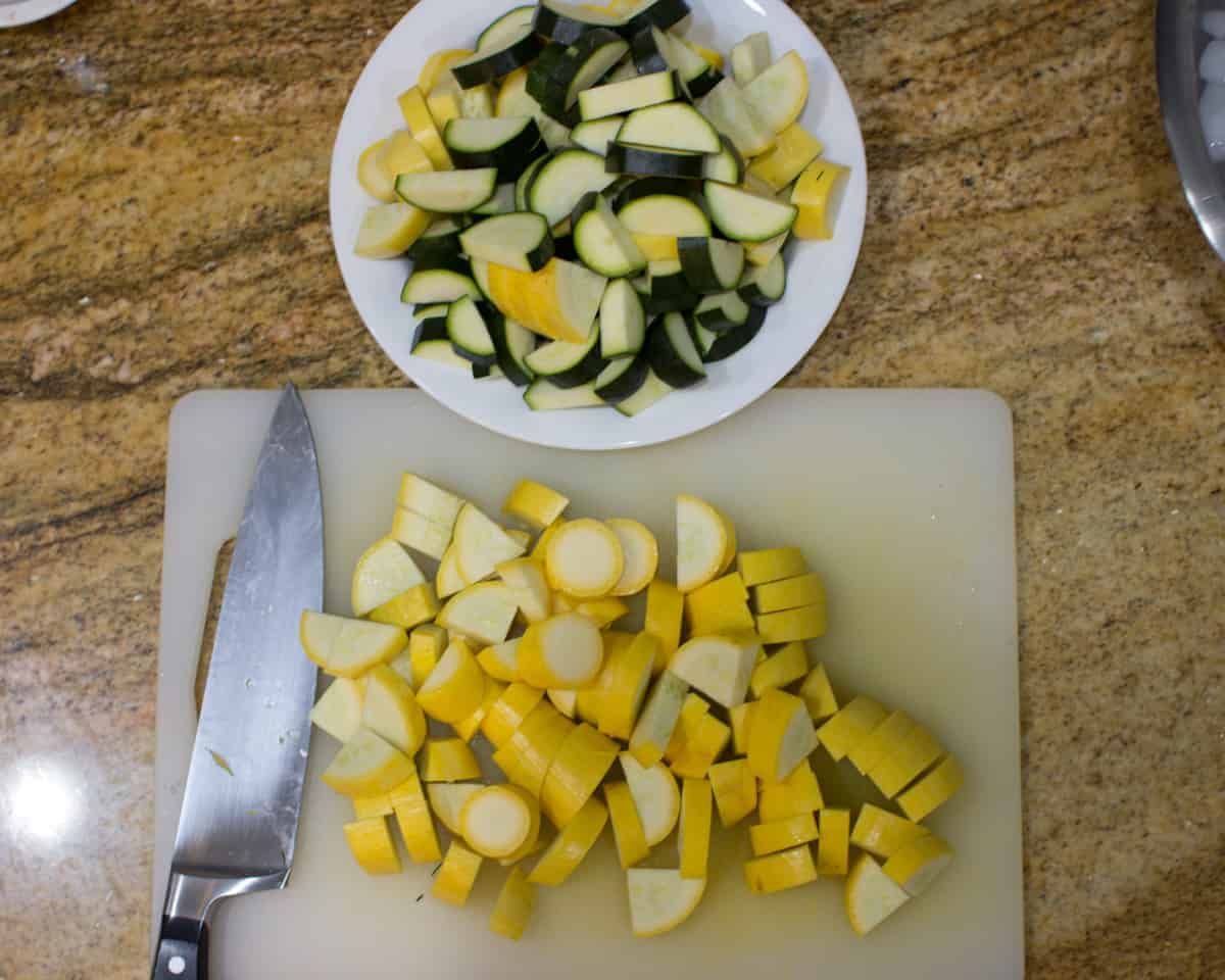 sliced yellow and green zucchini with a cutting board, knife and a bowl