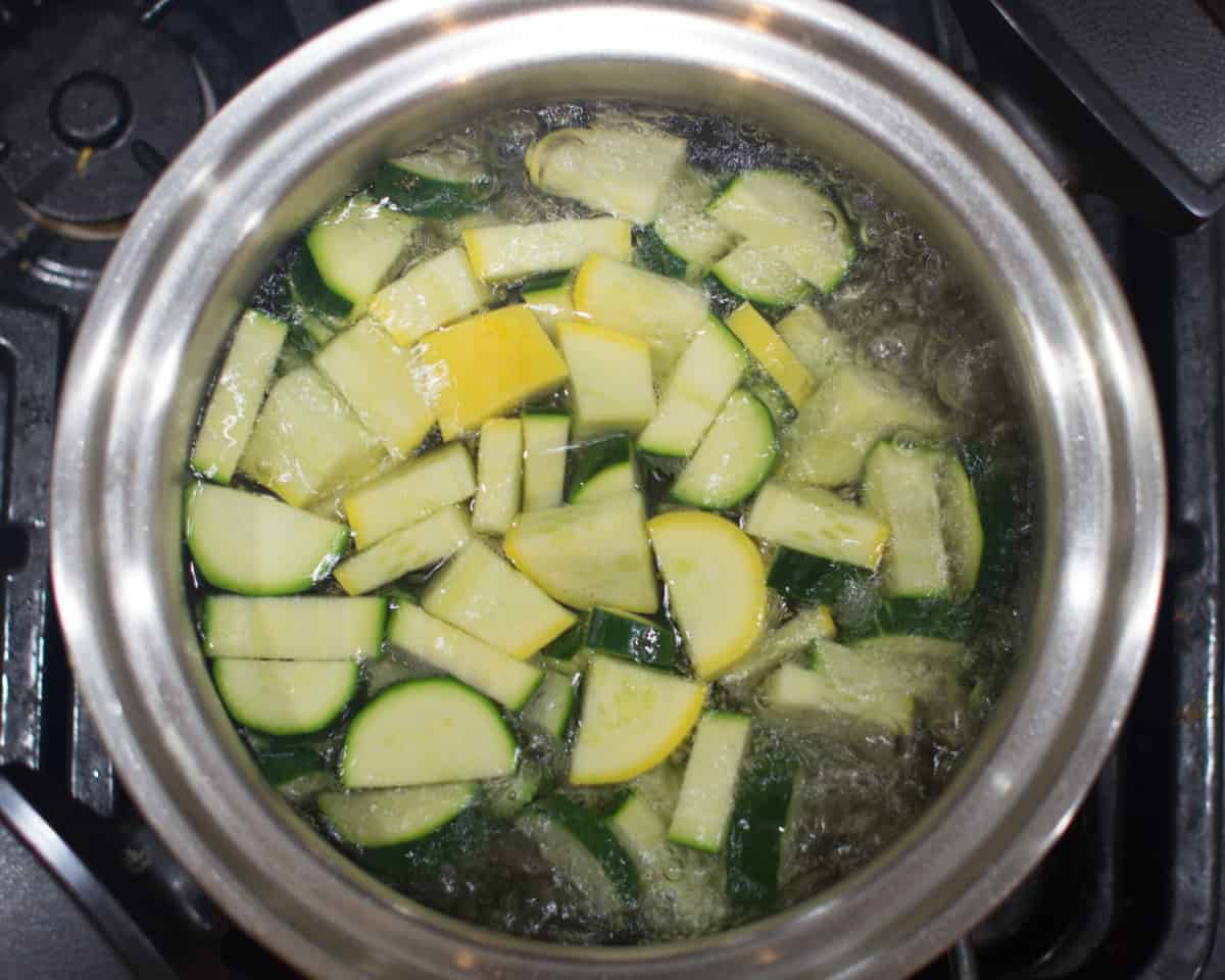 sliced zucchini in a large pot of boiling water