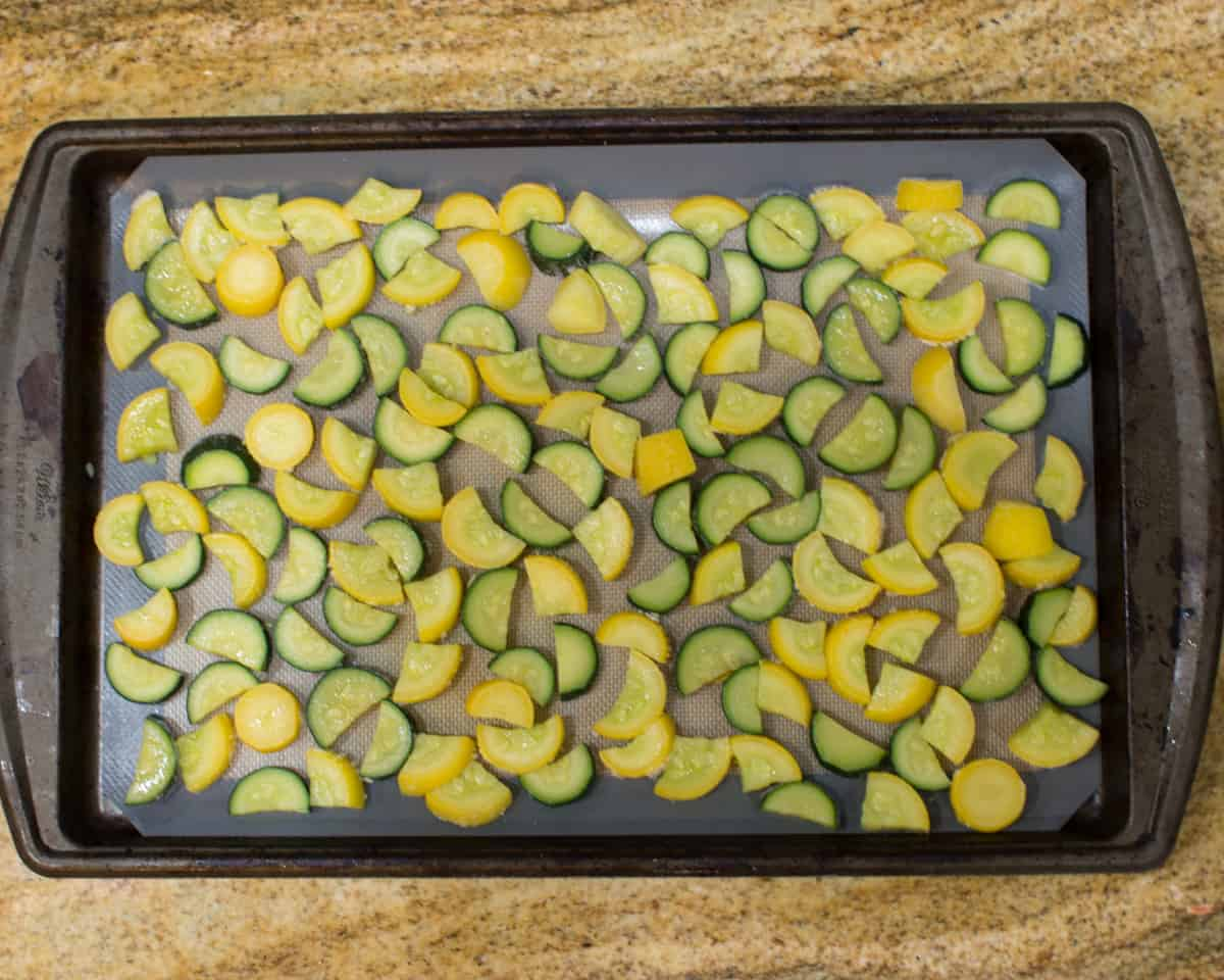 blanched zucchini lined on a lined baking sheet pan