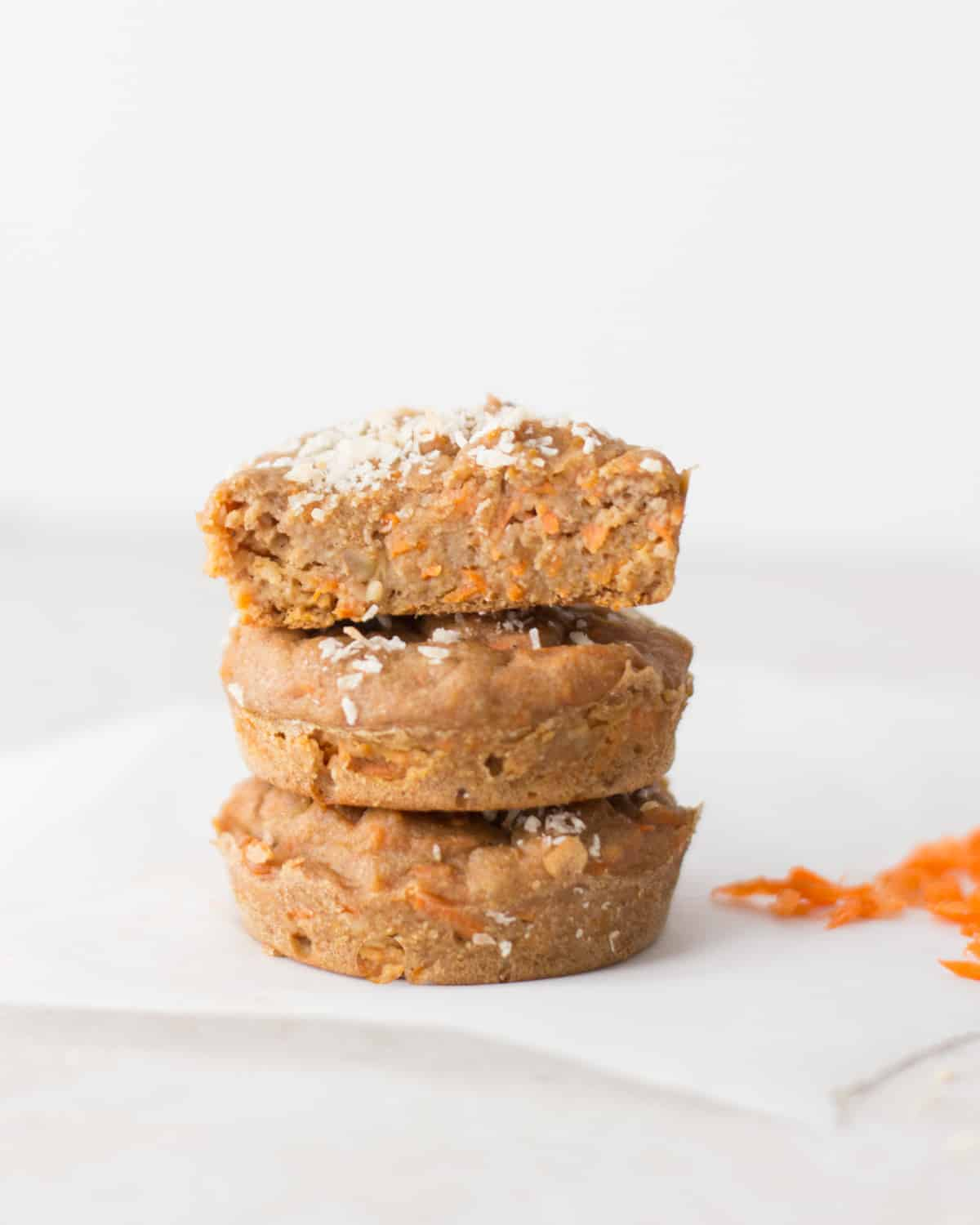 a closed up shot of three carrot oatmeal muffins stacked