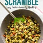 cooked veggie scramble in a skillet with green tipped spatula