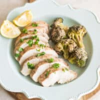 sliced chicken breast with a side of broccoli and squeezed lemon slices on a blue plate