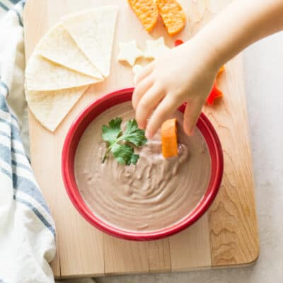 yogurt black bean dip in a large red bowl with a toddler hand dunking a sliced sweet potato