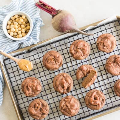 beetroot muffins on a wire rack with a spoonful of peanut butter, chickpeas in a bowl, and uncooked beetroot