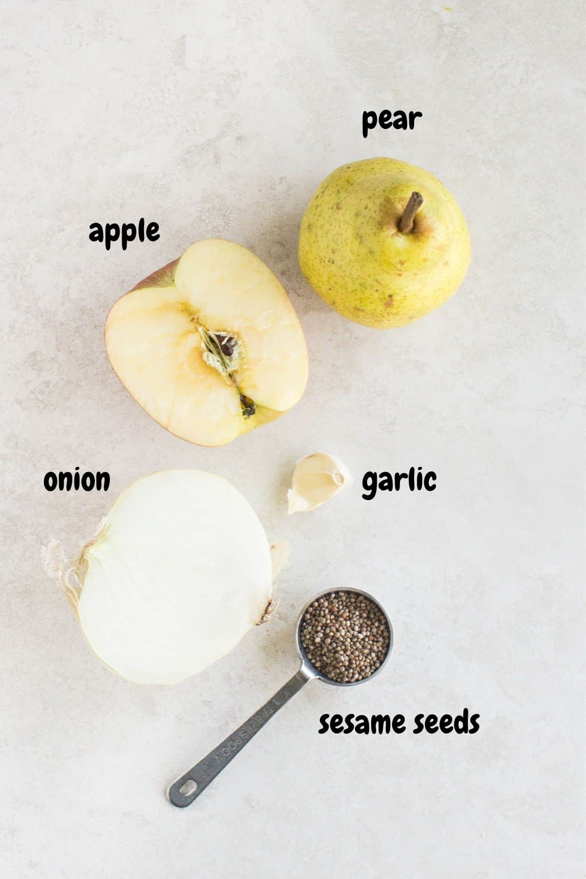 pear apple garlic onion and sesame seeds laid on a white background