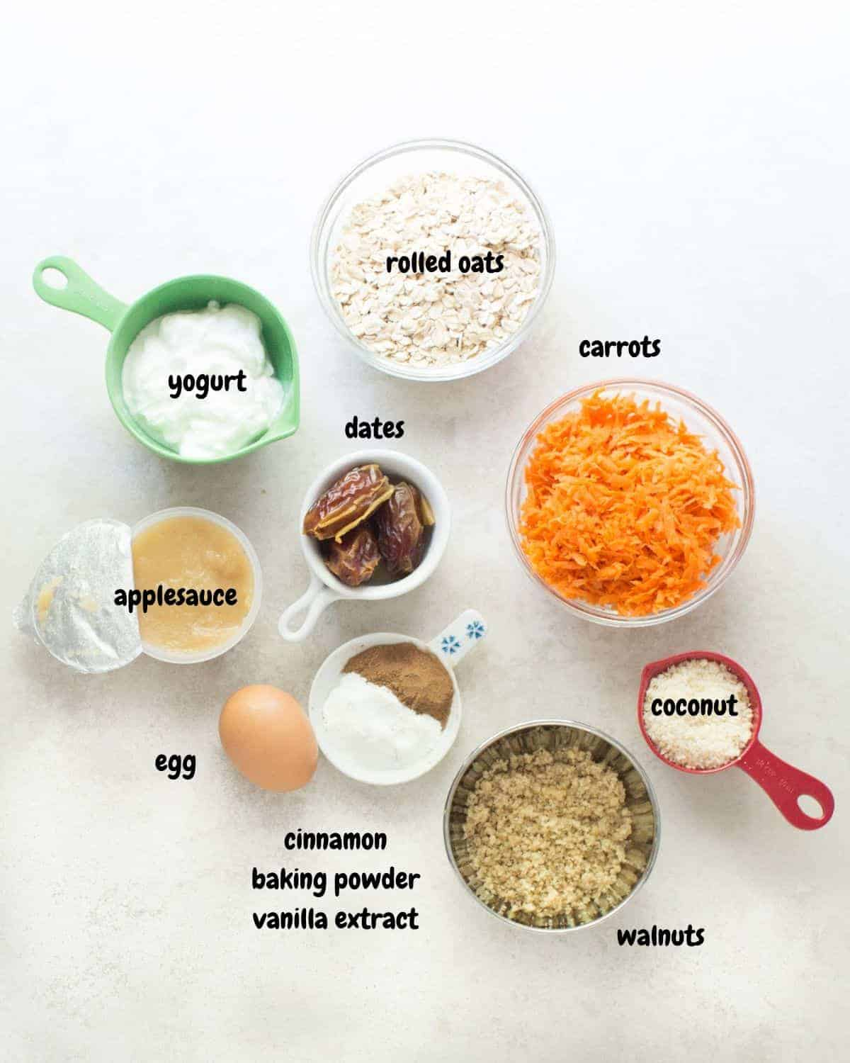 all the ingredients for carrot oatmeal muffins laid down on a white background