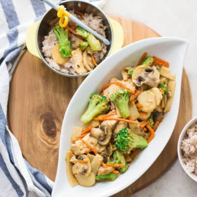 Chinese mushroom chicken plated on a large oval white dish and a bowl with rice and a small amount of the stir fry with chopsticks