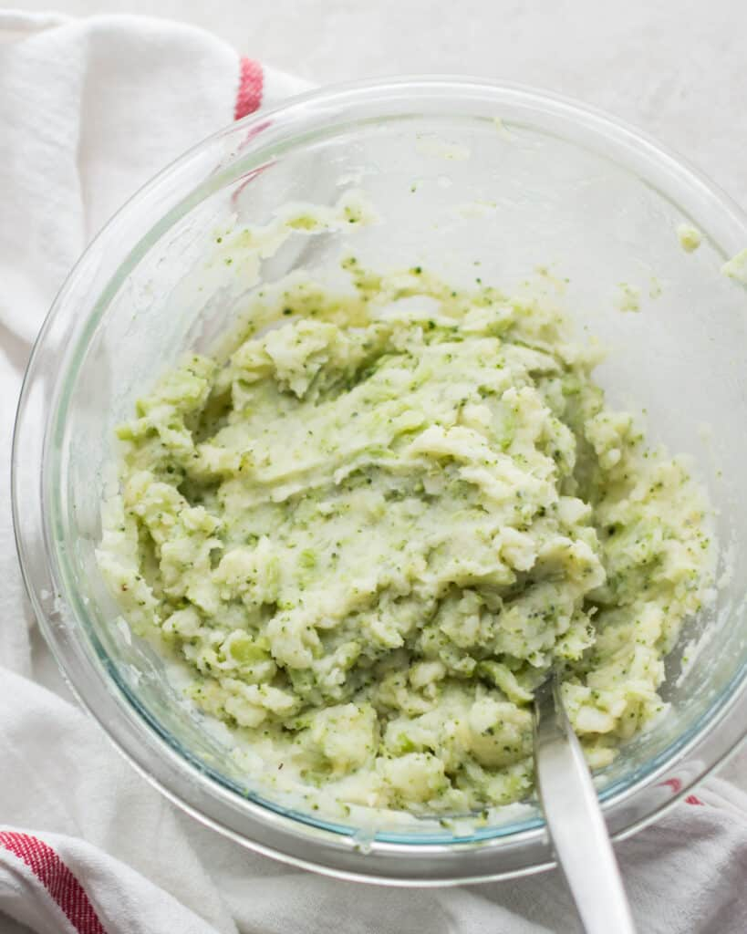 broccoli mashed potatoes in a large glass bowl with a fork
