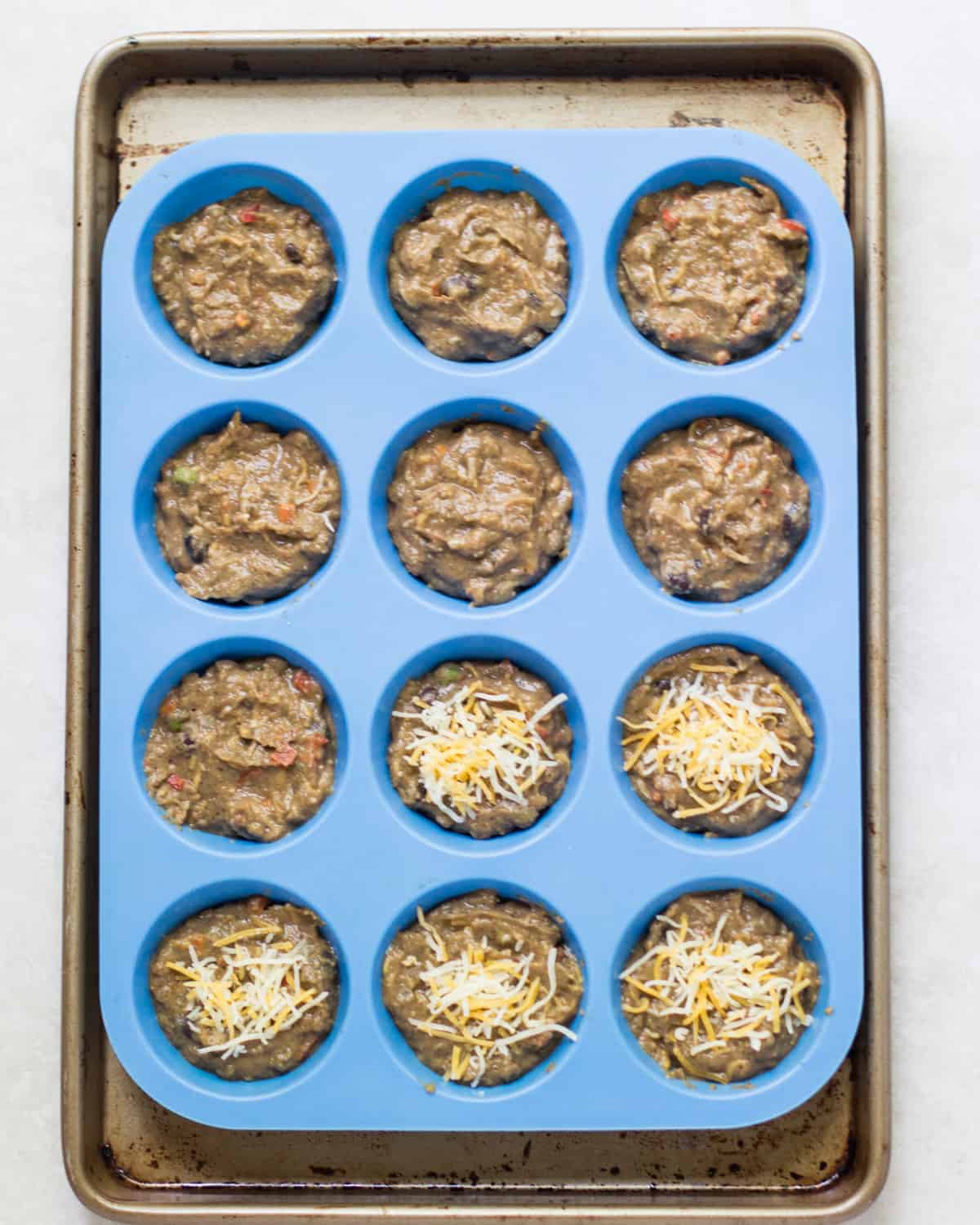 the mixture transferred to a 12 cup blue muffin silicone pan with 5 muffin stopped with cheddar cheese