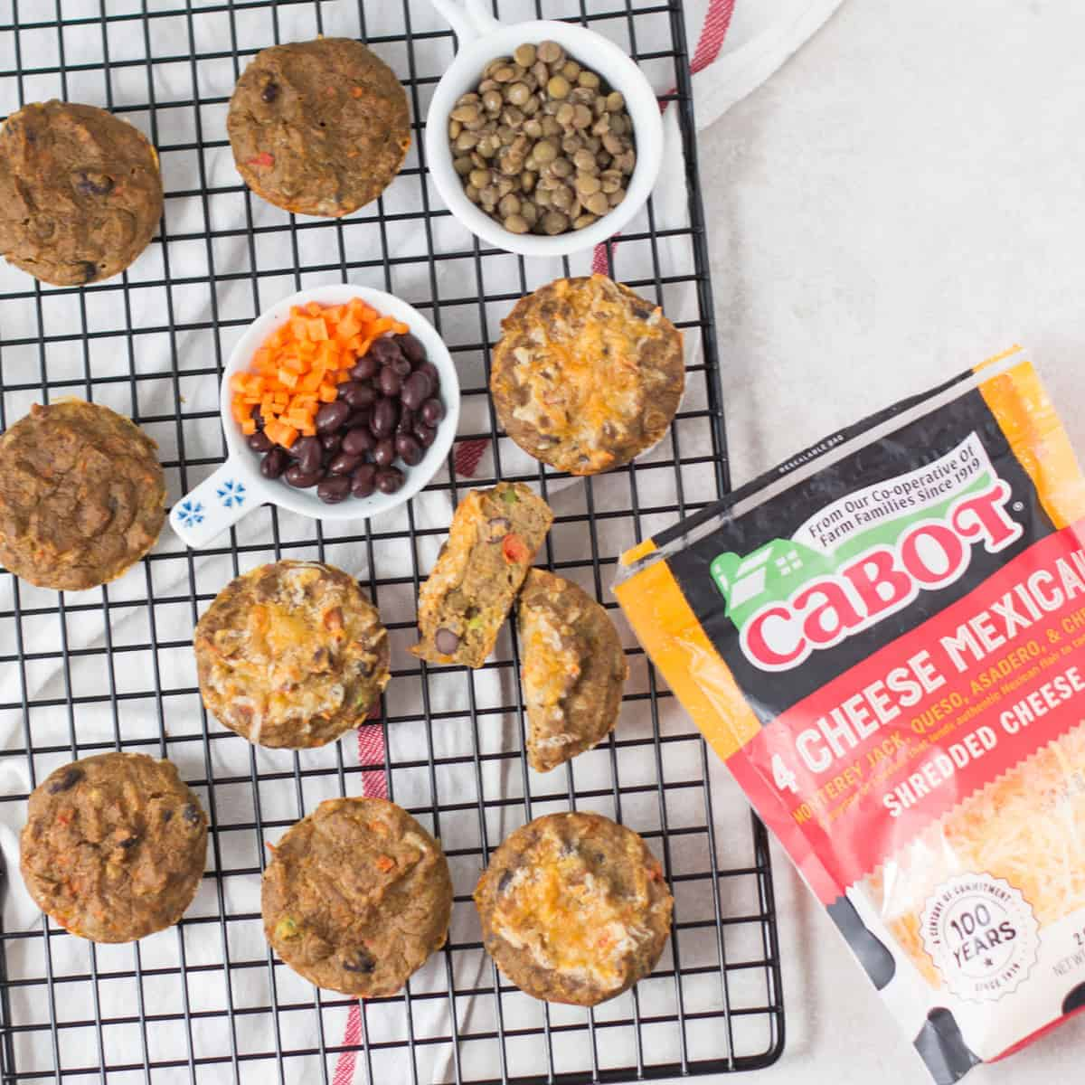 lentil muffins cooling on a wire rack with lentils, black beans, carrots, and Cabot Mexican cheese package