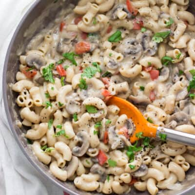cooked creamy mushroom pasta in a large skillet with an orange spatula