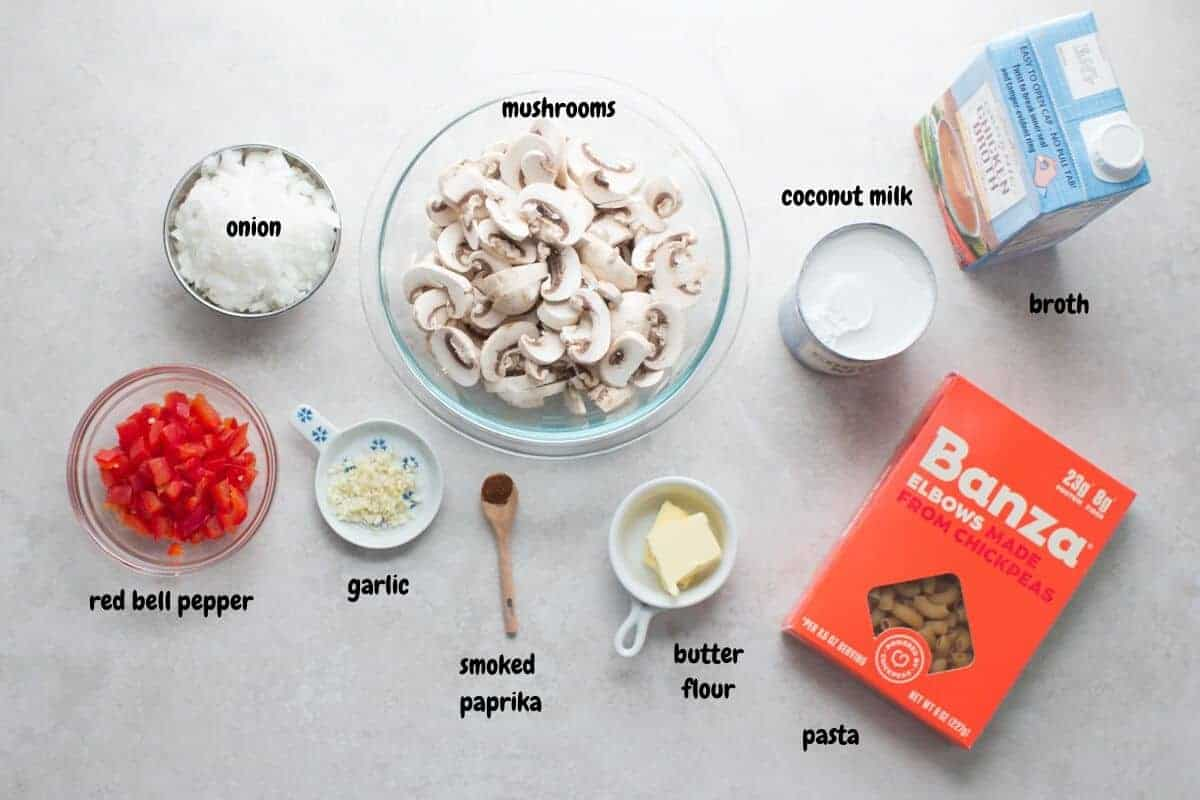 all the ingredients to make the mushroom pasta laid down on a grey background