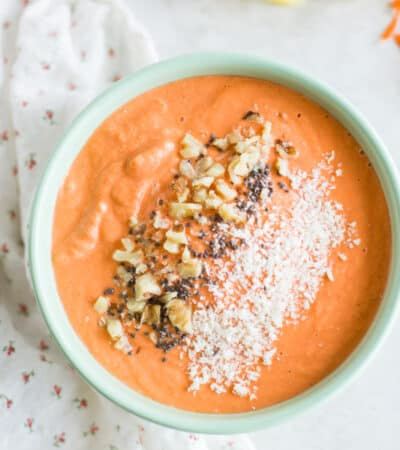 a close up shot of carrot cake smoothie bowl with ground walnuts, chia seeds, and coconut as toppings