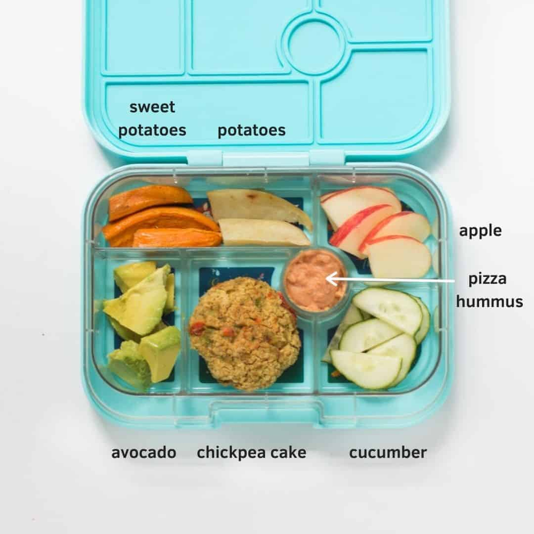 one chickpea cake with avocado, cucumber, apple, potatoes, and hummus in a blue lunchbox