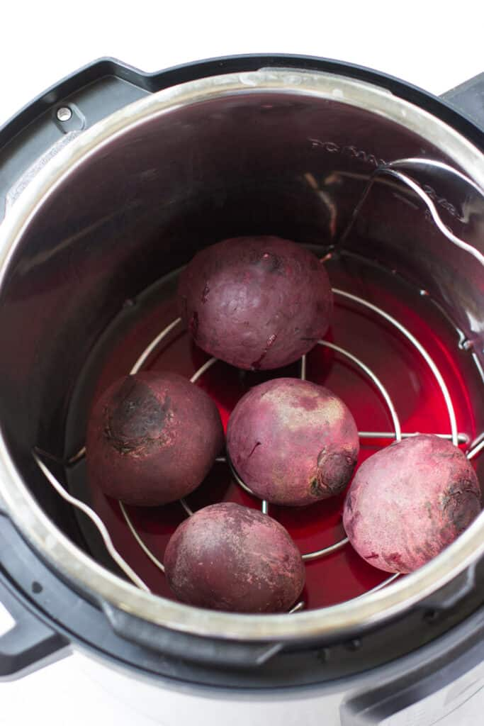 five cooked beets in an instant pot insert with a rack