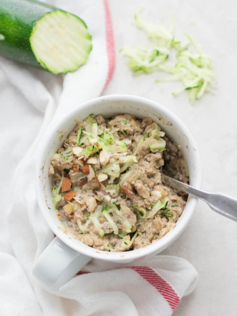 zucchini bread oatmeal in a white mug with shredded zucchini in the background
