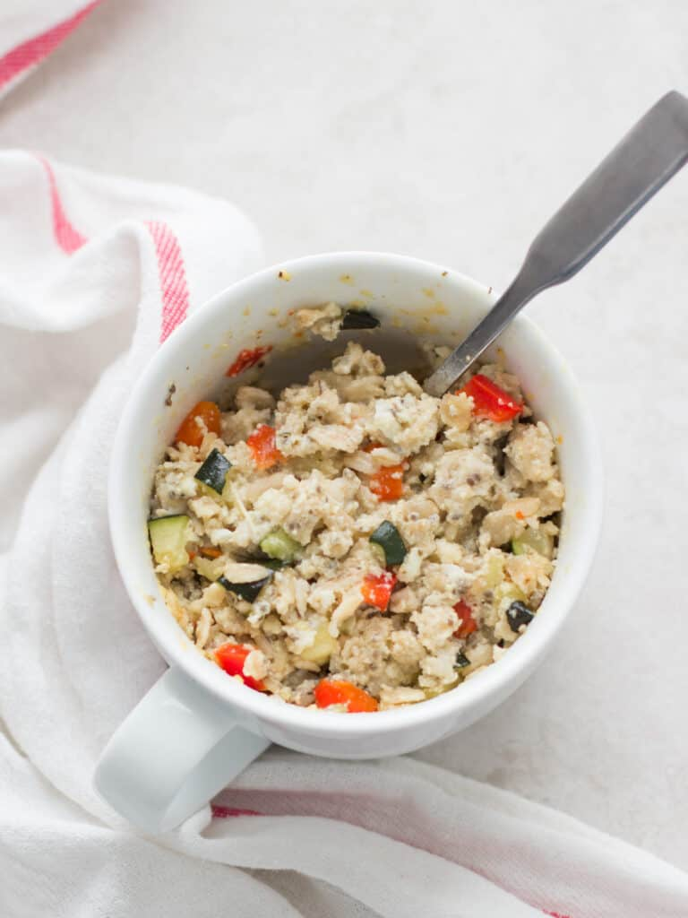 zucchini and bell pepper oatmeal in a white mug with a spoon