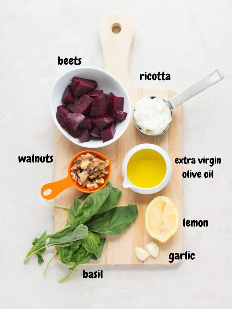 all the ingredients for pesto on a wooden board