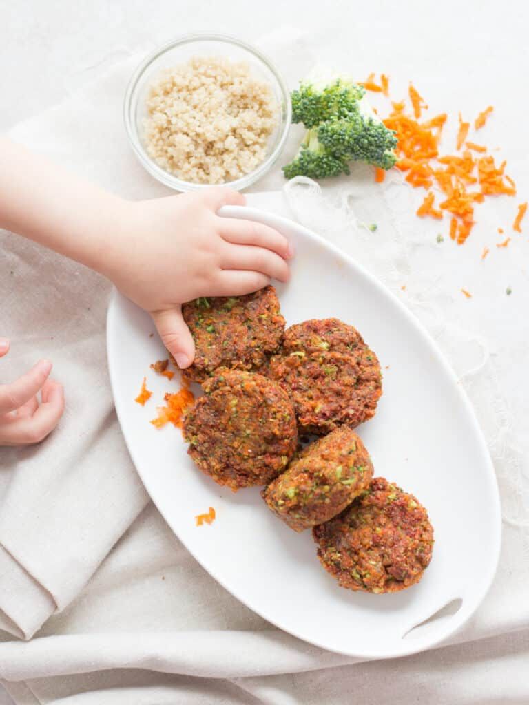 cooked vegetable muffins on a white plate with broccoli, carrots, and quinoa in background