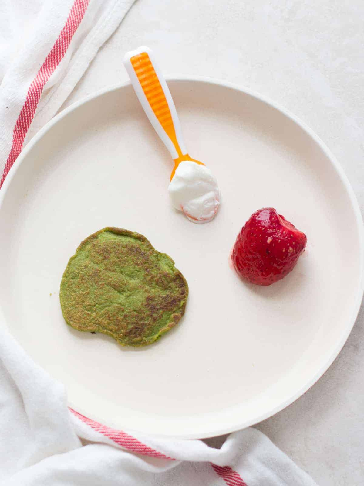 spinach pancake, Greek yogurt preloaded onto a baby spoon, and a strawberry serve on a white plate